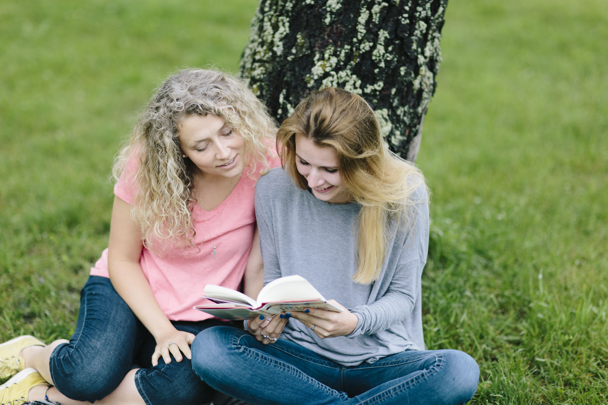 A mentor and teen sit outside and talk about a book they are reading