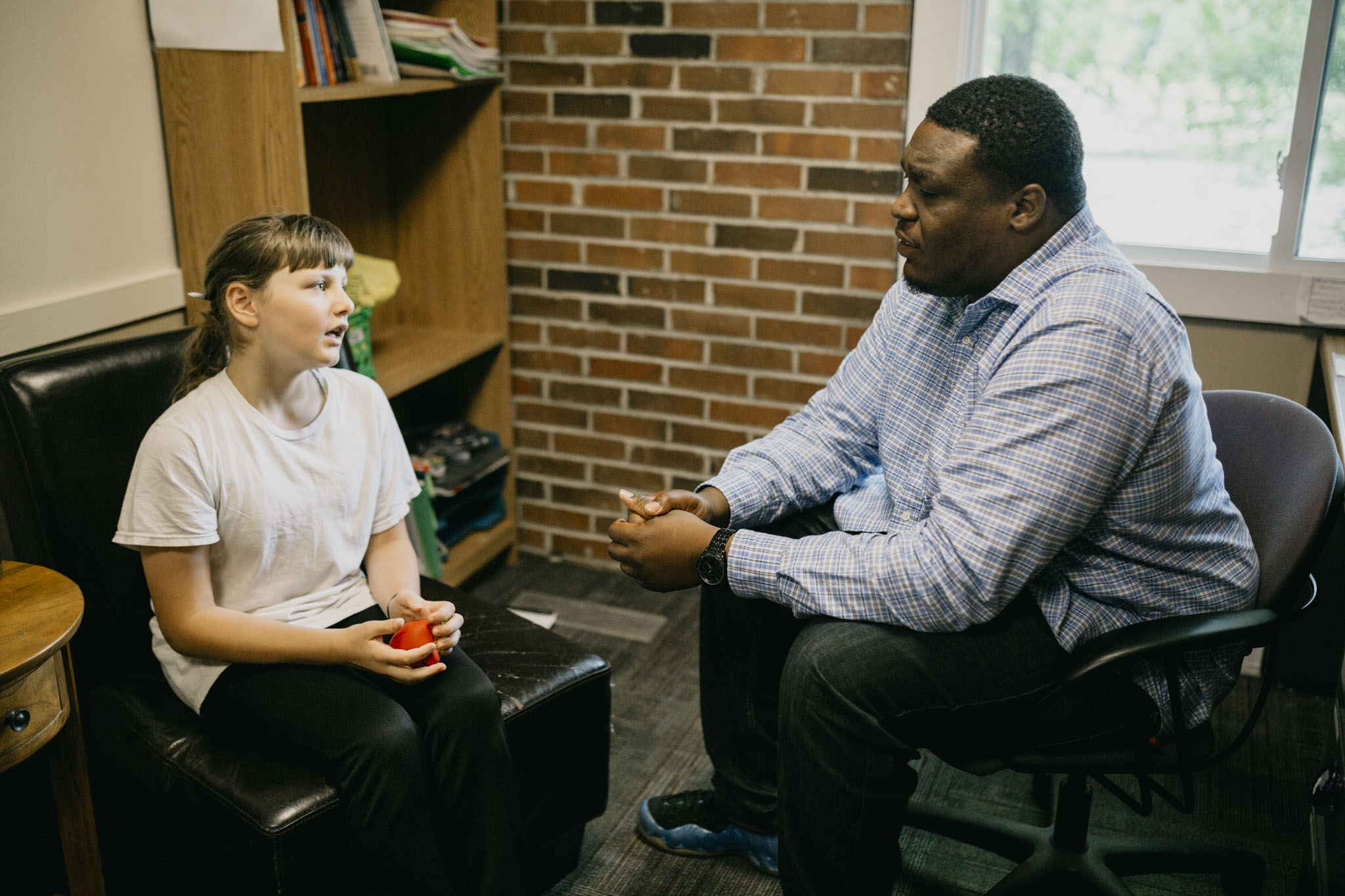 A preteen girl talks to her therapist during an individual therapy session