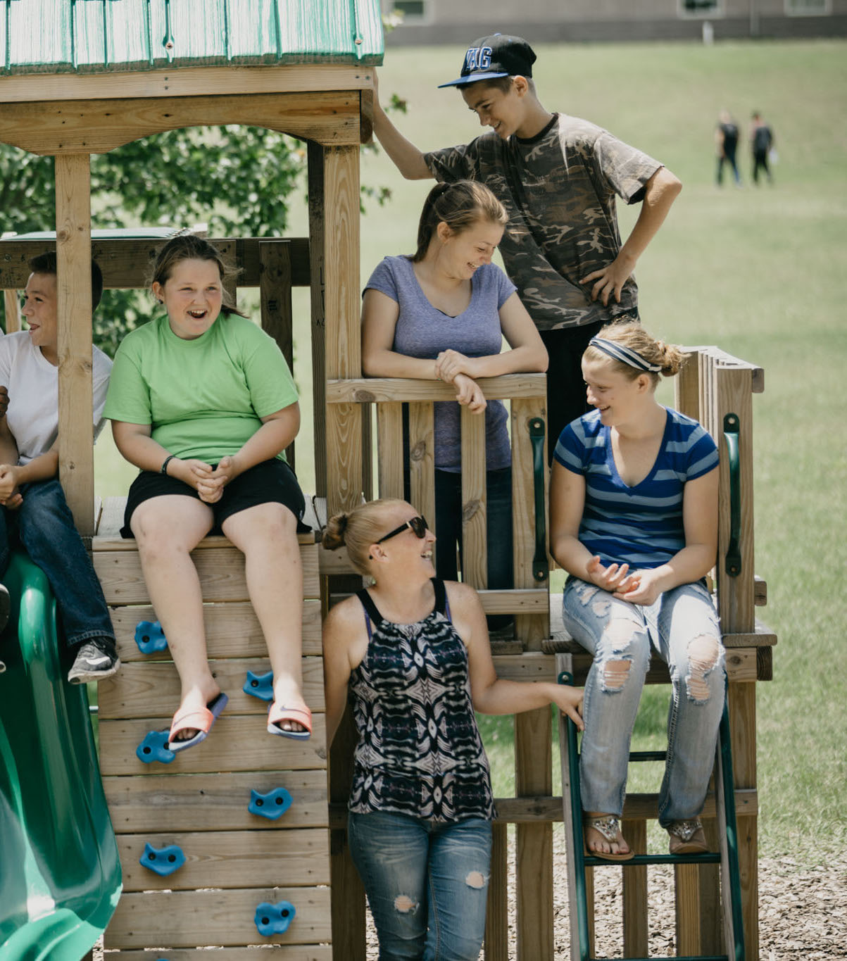 A foster care family hang out together at a playground