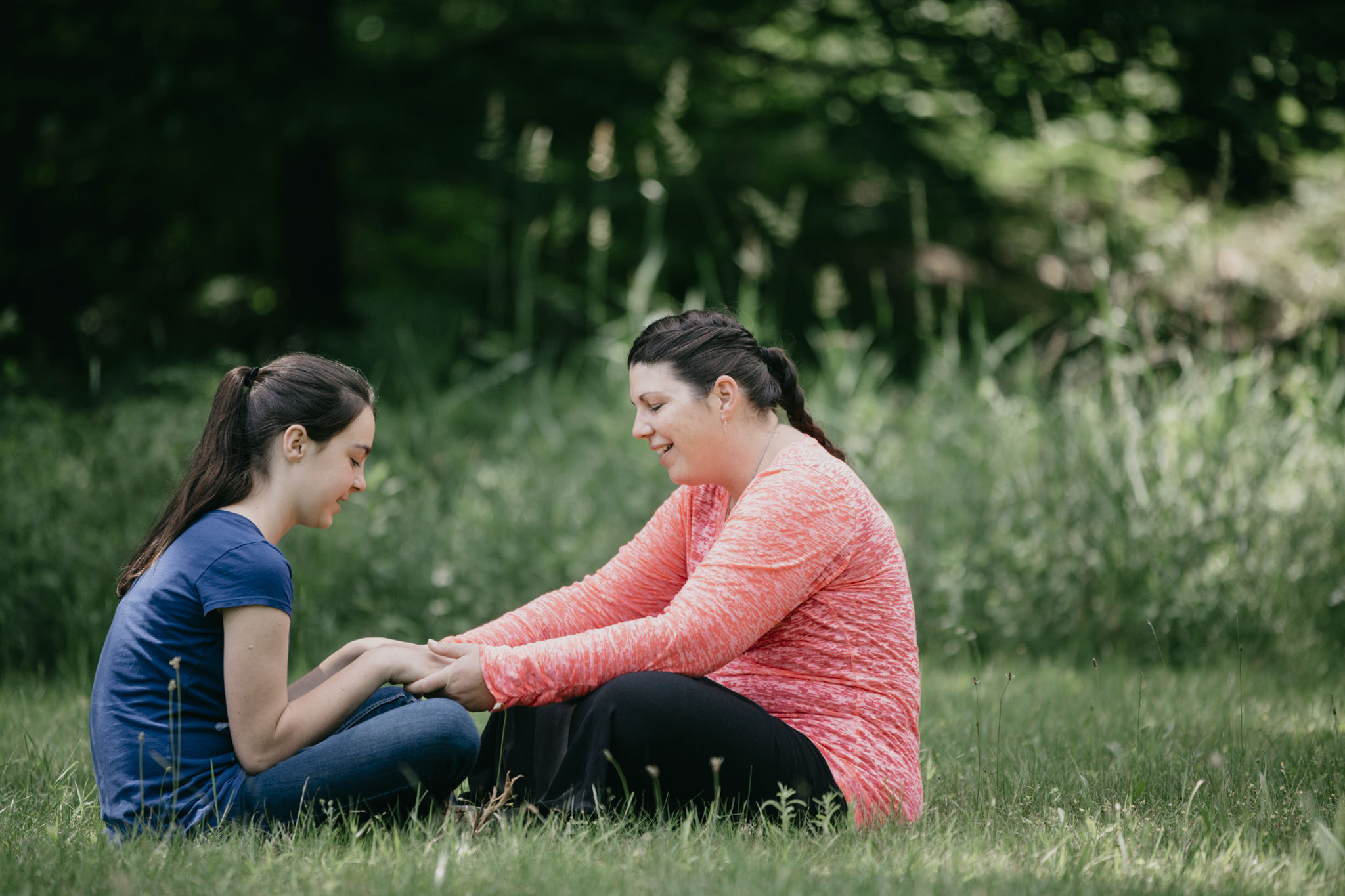 Mom and daughter sit in the grass to talk about their family after gaining new skills at Eagle Village