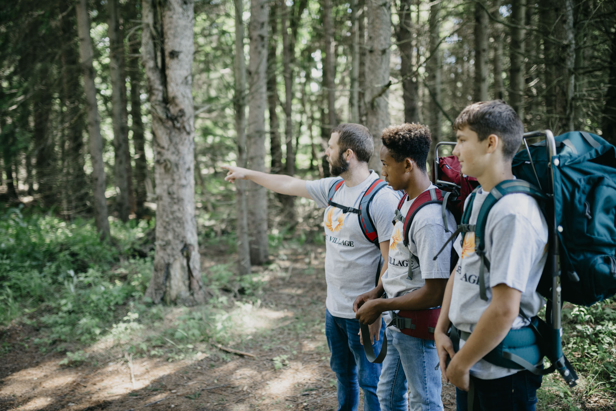 Two teens receive instruction from a staff on how to hike to the next location of events during their intervention summer camp