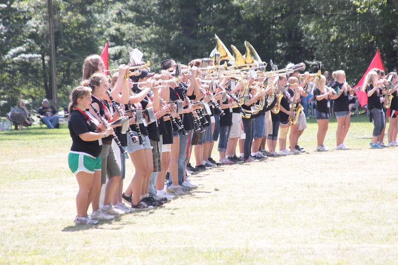 A high school band uses a training field to practice their formations