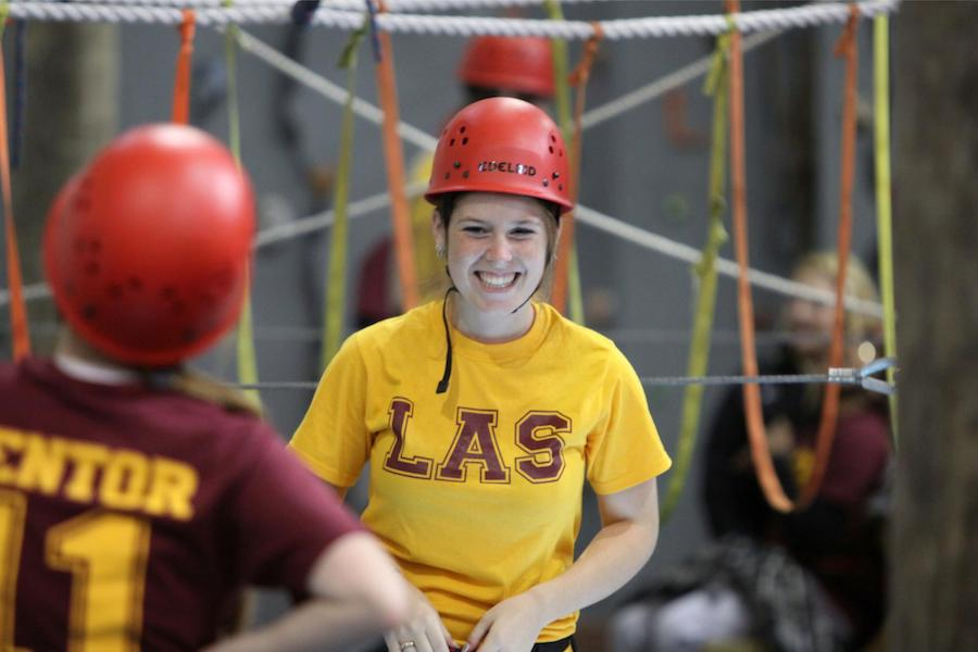 A college student stops to smile before heading up into the indoor ropes course