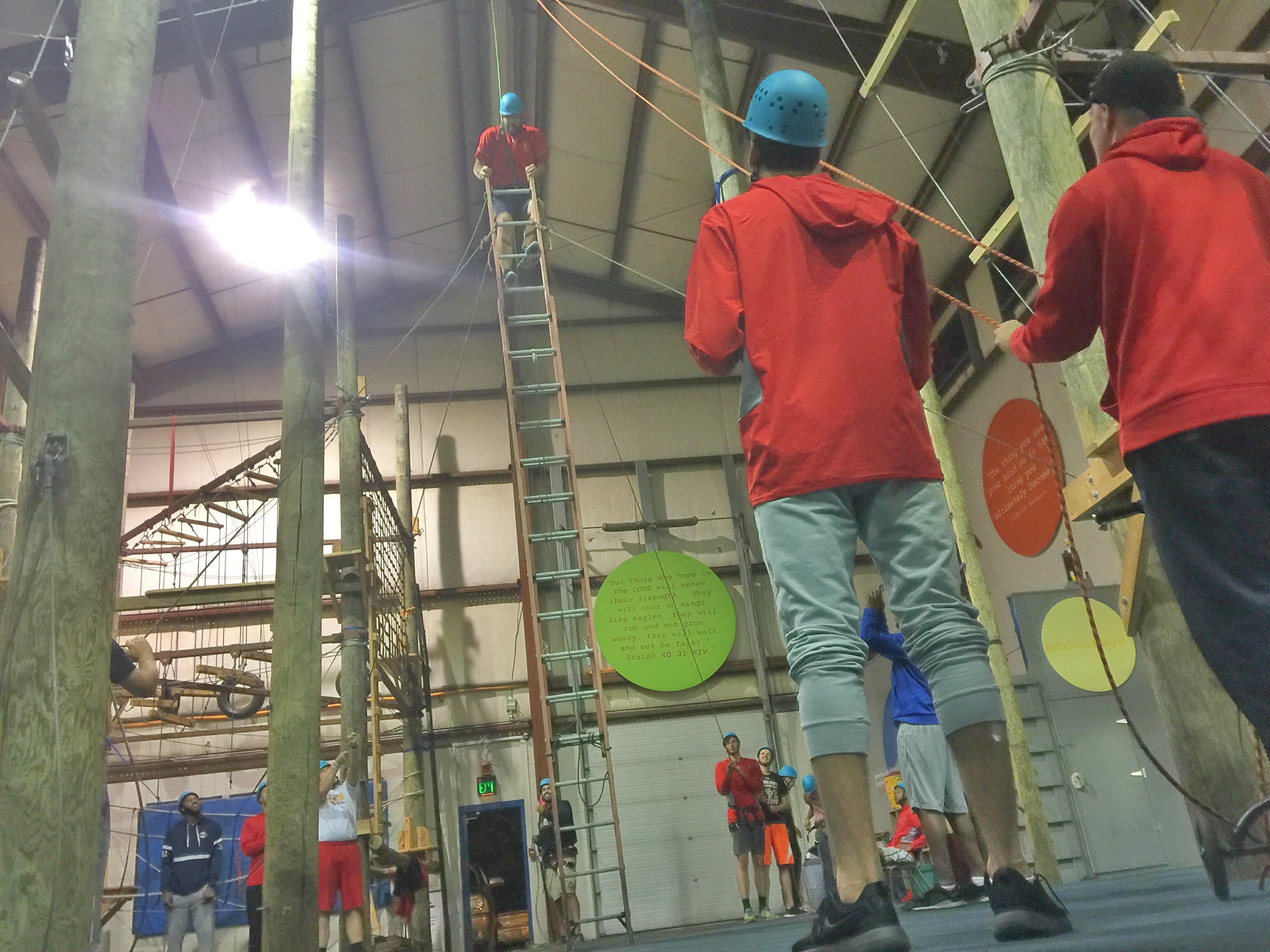 A college team uses tension ropes to hold a ladder in place while a teammate climbs to the top.